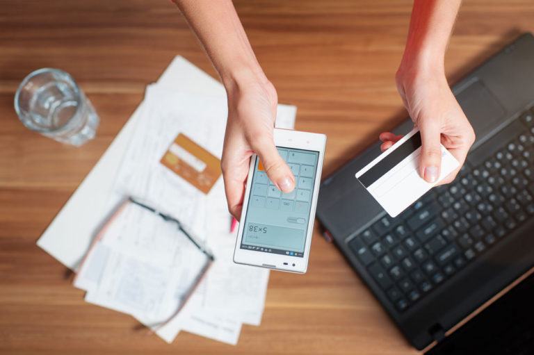 Short Pays: women using calculator on phone holding credit card at desk